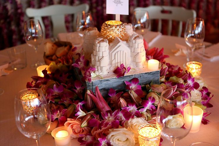 Wedding seaside dinner centerpiece with sand castle, tropical flowers and tea light candles
