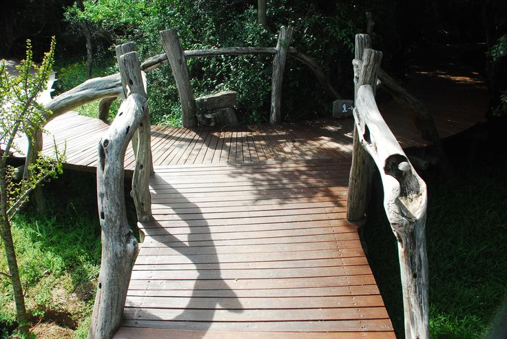 The raised walk ways are created to leave less impact on the earth and the railing is logs from the forest (note the little mushroom carved on the right) Sibuya Game Reserve Forest Camp reached via boat along the Kariega River from Kenton on Sea, Eastern Cape, South Africa www.sibuya.co.za