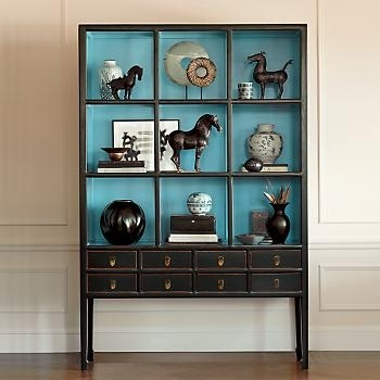 Organize a collection in a cabinet and make a design statement. Old china cabinets with the doors removed and painted complimentary colors make a unique display curio for an assorted display of accessories, books, and photos.