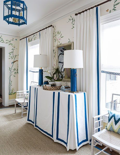 For the upstairs hallway, Christopher Nutter channeled a look of cheerful chinoiserie with hand-painted walls by Gary Goldberg, a scalloped lantern by Coleen & Company, and white bamboo trellis armchairs.:
