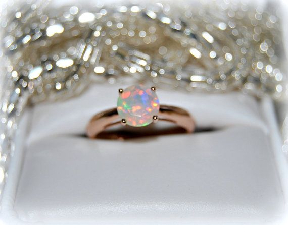 This opal solitaire rose gold engagement ring is offering a symbol of love marked by an everlasting joie de vivre to every couple exchanging vows. Set with one Queen of gems opal it is dazzling with splendid radiance. Fashioned from 14k rose gold. Contemporary elegance meets timeless appeal.  Features: Gemstone: 0.85ctw round opal, natural, no treatment, solitaire, faceted. Metal: 14K rose gold Size 7  New old stock. Note: The quality of our Customer Service is one of our top priorities. We…