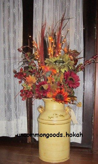 An old milk can holds Fall florals and lighted branches; great porch or entry door display.