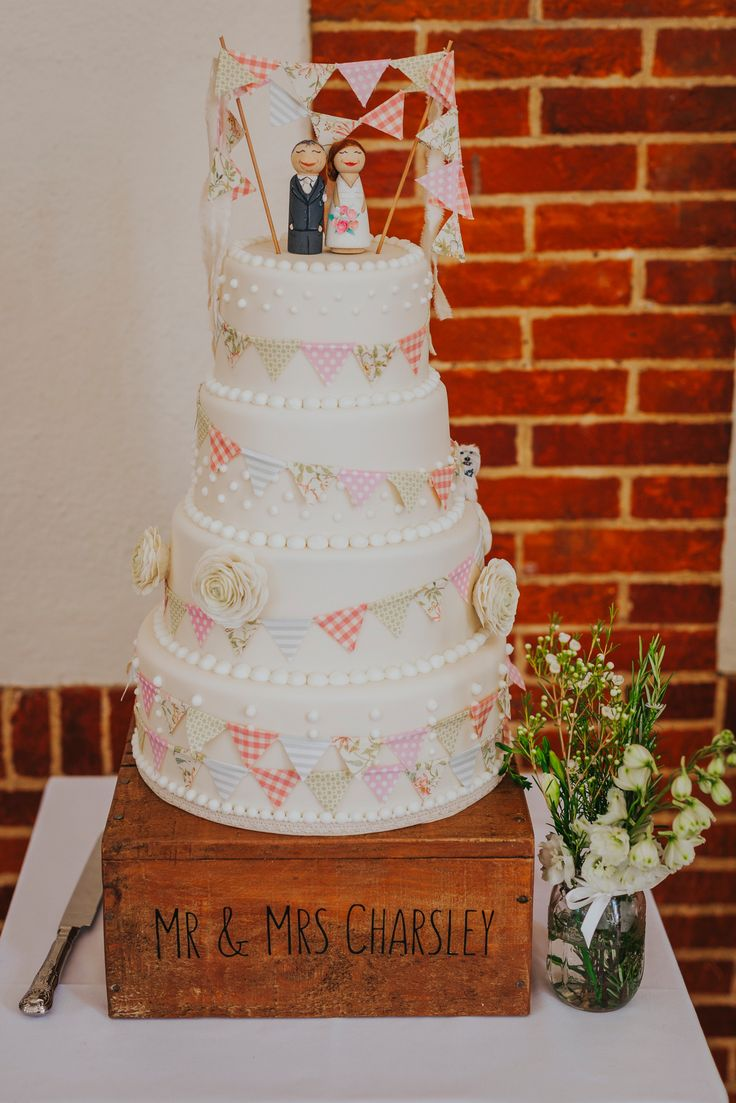 Gorgeous, elegant and fun - the bride and groom's personalised wedding cake. Can you spot their dog hiding on one of the tiers? Photo by Benjamin Stuart Photography #weddingphotography #weddingcake #buntingcake #tieredcake #countrywedding #cakeideas