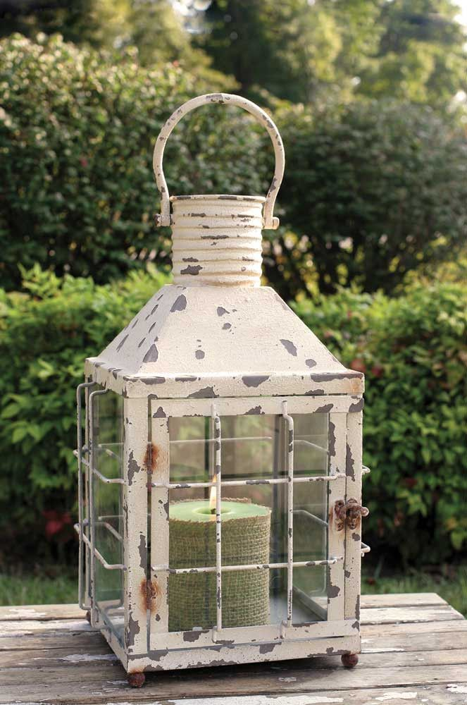 """This cream lantern measures 10"""" square and 21"""" tall to top of handle. Features a door with a latch to access candle and other items inside the lantern. Top is open to allow for ventilation. Comes in a"""