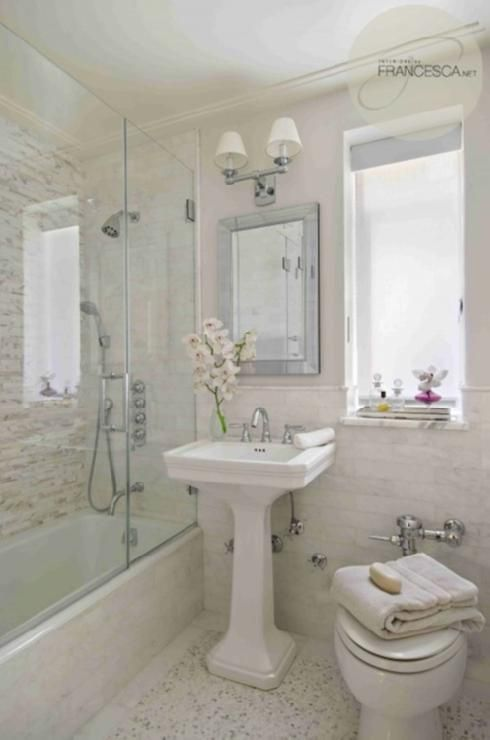 Absolutely gorgeous bathroom with glossy white pedestal sink, soft gray walls paint color, beveled mirror, double sconce, calcutta gold marble subway tiles backsplash with pencil rail, seamless glass shower with mosaic stacked linear tiles shower surround, marble mosaic inset tiles floor and mirrored tray.