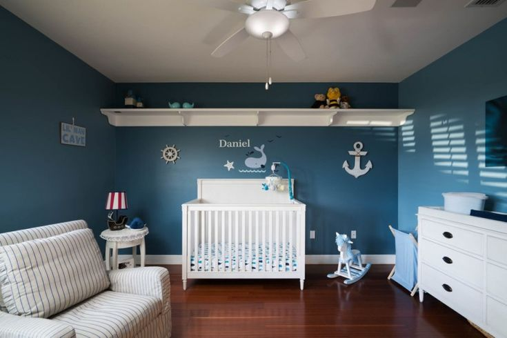 navy blue theme boy room with blue painted wall with stickers, stripped blue white couch, white cribs with blue white linen, white table, white cabinet, blue laundry basket, white fan lamp, toys