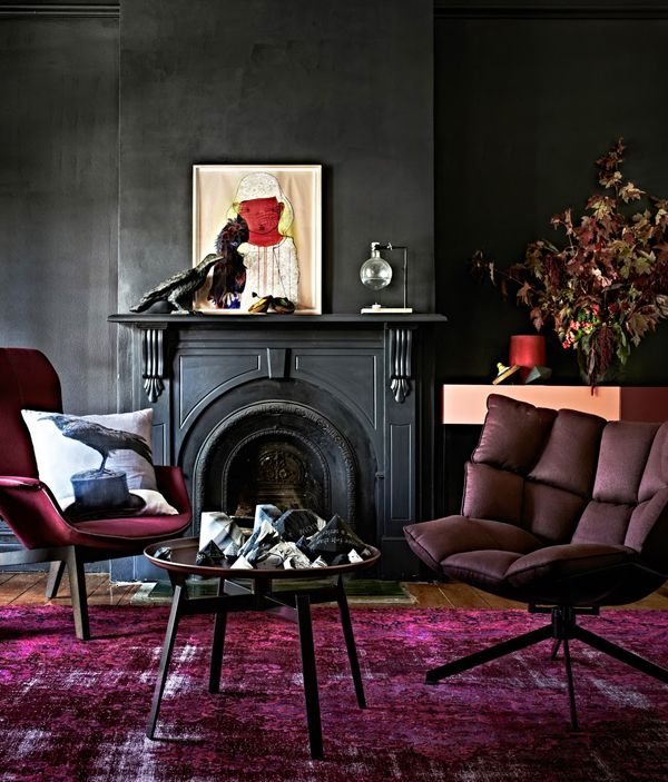 inky black living room with rich purple rug. Go large with the rug and Place the chairs and sofa on the rug for a unified look.
