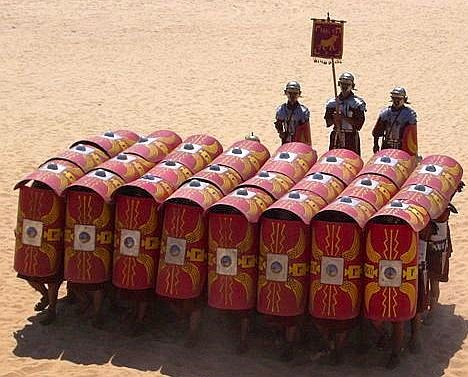 "Roman testudo (tortoise) formation.  In Ancient Roman warfare, the testudo or tortoise formation was a formation used commonly by the Roman Legions during battles, particularly sieges. Testudo is the Latin word for ""tortoise"". The Greek term for this formation is ""chelone"" and during the Byzantine era, it seems to have evolved to what military manuals of the era call the ""foulkon""."