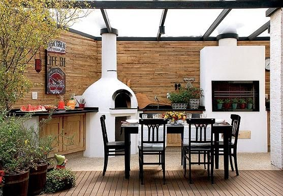 Varanda de residência térrea coberta com teto de vidro leitoso e com churrasqueira e espaço gourmet