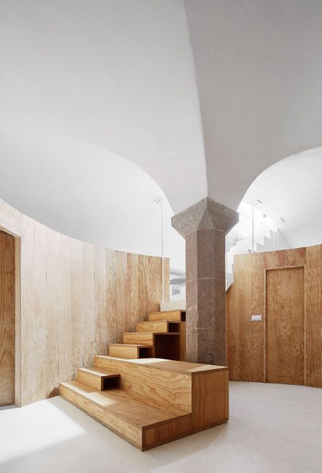 Circular pine wall creates rooms in vaulted basement home by Raúl Sánchez.