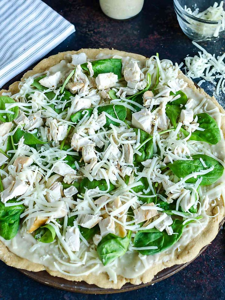 homemade white pizza ready to put into the oven topped with white sauce, chicken, spinach leaves and cheese