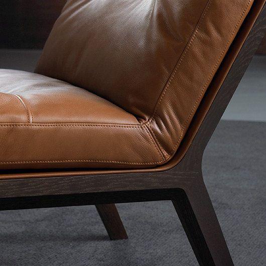 Einladende Polster, weiches Leder mit eingenähtem Keder, das fein nach innen geformte Holz ergänzen einander zu einem feinen Fauteuil. Minimalistische Formensprache und opulente Materialien.