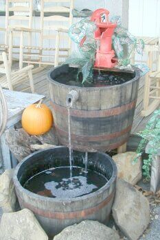 This multi tiered barrel fountain is made with vintage Kentucky Bourbon whiskey barrel  halves. Just add a pump, and in this case a cast iron hand pump for a soothing deck, patio, yard, or garden addition