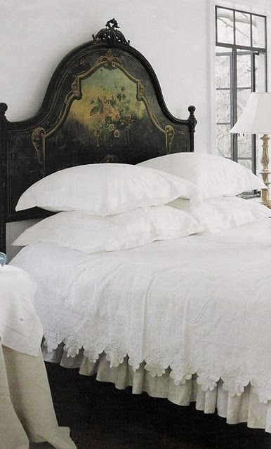 crisp white bed linens and white walls contrast beautifully with the dark painted headboard