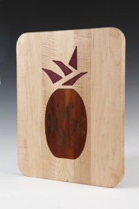 "Cutting Board Inlaid with Pineapple Design by Kentucky Cutting Boards. $77.95. Food-safe glue, cut on the back. www.kentuckycuttingboards.com. Appalachian Maple, Made in America. 10""x14"" w/ rounded corners, USA Made. Cherry, American Walnut and Maple. Kentucky Cutting Boards are Made in the USA.  All of our cutting boards are made from sustainable yield hardwoods and support our region's hardwood industry.  The side of every board is stamped with our signature horseshoe brand to ..."