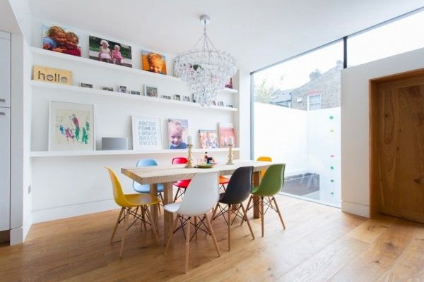 In this playful dining room, the designer has chosen a rainbow of Eames chairs which work nicely against the warm wooden floor and white wal...