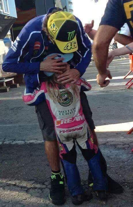 Valentino Rossi hugging a little fan.