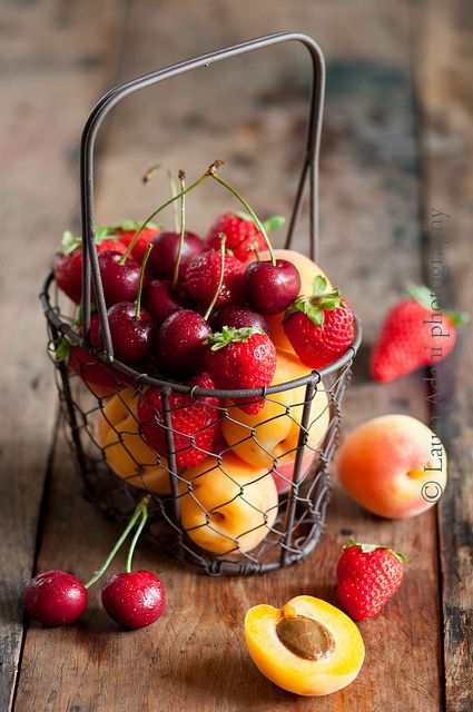 Metal basket filled with apricots, strawberries and bing cherries