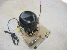 Vacuum Pump - Homemade vacuum pump constructed from a surplus refrigerator compressor, tubing, and valves.