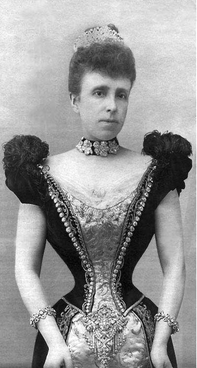 After 1879, Queen Maria Cristina of Spain, wearing her famous devant-de-corsage suspended below her waist.