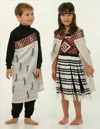 2 kids with cloaks on, that are bordered with taniko pattern