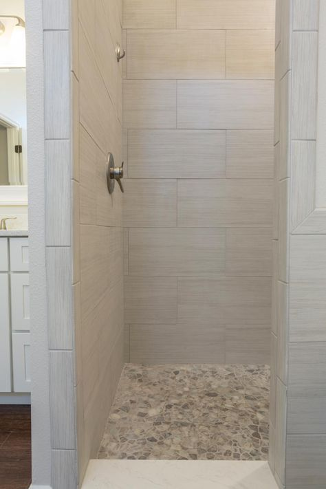 Sleek yet soft gray tiles carve out a gorgeous walk-in shower in this transitional bathroom. Pebble tile floors in gray tones coordinate with the walls while adding striking interest underfoot.