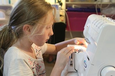 STUDENT LEARNINGTO USE AN OVER LOCKER IN TEENAGE - JUNIOR LEARN2SEW WORKSHOPS
