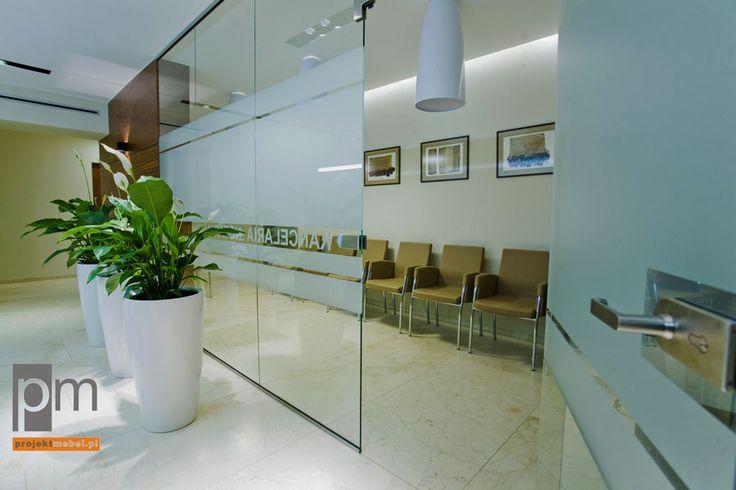 Na szklanych płytach również znalazł się napis, co sprawa, że miejsce nie jest anonimowe. Z kolei pokrycie szkła w środkowym pasie mleczną fakturą czyni przestrzeń biura niekrępującą zarówno dla klientów, jak i dla zajętych swoimi obowiązkami pracowników. http://www.projektmebel.pl/meble-biurowe-do-kancelarii--od-drzwi-do-biurka