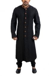 Poonam Kasera brings to you an exceptional traditional kurta with intricate details that will floor you at first look. The black kurta is adorned with cut dana work between the pintucks which is bound to give you a slimmer look. Patchwork in ethnic block printed fabric lines the stand collar and the cuffs and also covers the seven buttons in the front. Wear the outfit to an evening do with a matching pair of churidar pyjamas or jodhpuris and you are bound to make heads turn.
