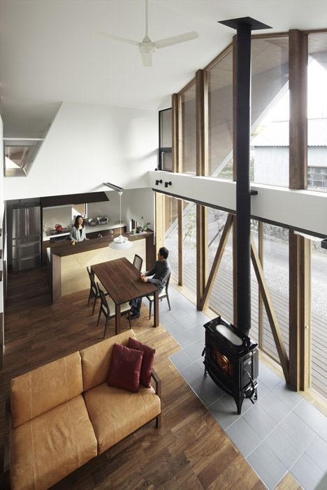 The interior of this Japanese house centres around a double-height living room with a kitchen and dining room on one side