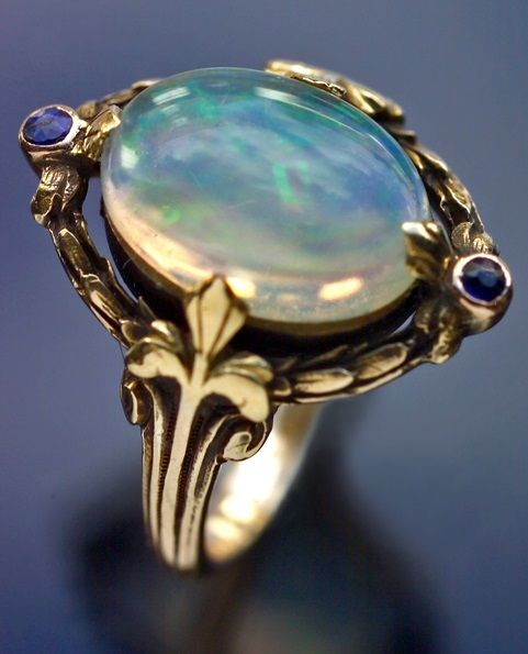 SIBYL DUNLOP Arts & Crafts Ring. Gold, water, opal, sapphire. H: 1.8 cm (0.71 in). British, c.1920.