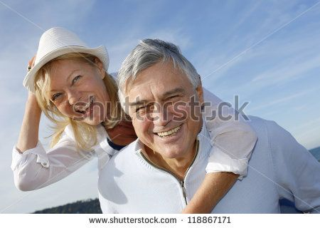 Portrait of cheerful senior couple having fun at the beach - stock photo