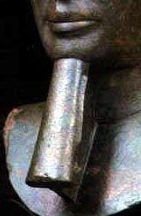 Uma barba de cerimônia trançada e postiça é outro dos atributos do rei e até a rainha Hatshepsut (c. 1473 a 1458 a.C.) se fez representar com ela. É de se notar que o faraó não só é geralmente imberbe, como também manda raspar o crânio no dia da sagração. Aqui a barba aparece representada no rosto de um dos Ptolomeus, num busto feito de bronze.