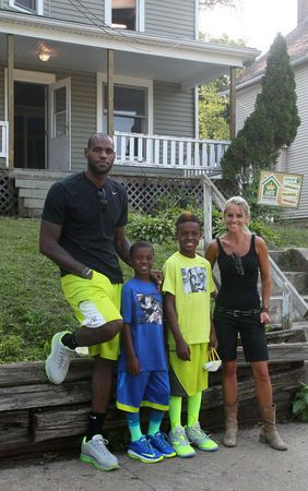 """TV's Rehab Addict host Nicole Curtis, right, poses with LeBron James and his sons, LeBron Jr., and Bryce at a rehab site on Monday, Aug. 4, 2014, in Akron, Ohio. James took the controls of a backhoe to help fix up a crumbling house for the family of a sixth-grader in his Wheels for Education mentoring program. Work on the house will be featured later on Curtis' show """"Rehab Addict"""" on the HGTV network."""
