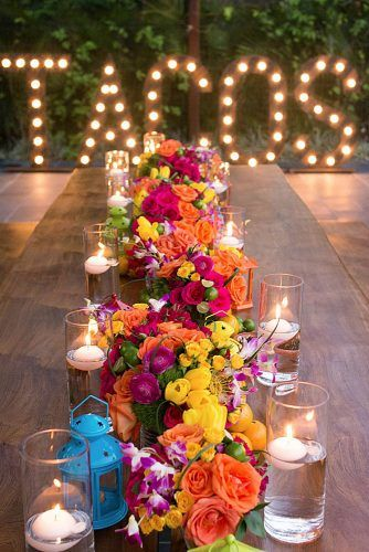 wedding taco bar on a long table bright flowers and candles on the background inscription tacos with light bulbs bohemiadelmar