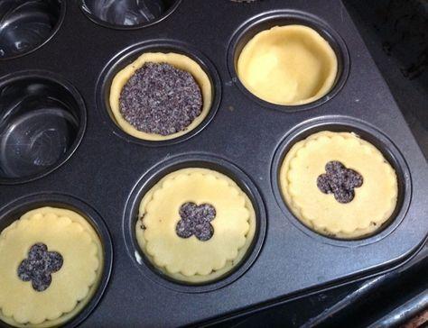 Křehké makové koláčky, krok 3: Troubu předehřejte na 190 stupňů, formu na muffinky vymažte máslem. Těsto vyválejte do tenka a vykrojte kolečka s průměrem o něco větším, než jsou otvory pro muffiny. Kolečky vyložte otvory formy, lehce přimáčkněte a naplňte makovou náplní. Ze zbytku těsta vykrojte kolečka o velikosti muffinového otvoru, vykrojte do nich třeba kytičku nebo hvězdičku a položte na makovou náplň. Lehce přimáčkněte. Dejte péct do vyhřáté trouby asi na 20 minut, až lehce zhnědnou.
