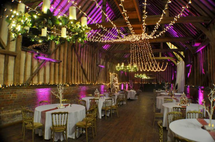The barn at Lillibrooke Manor with deep pink uplighting and a fairy light canopy