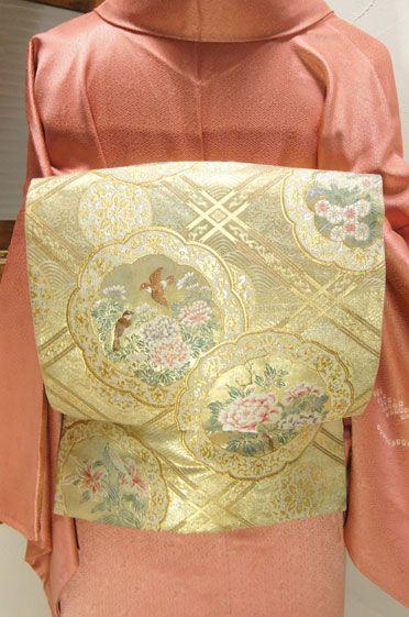 四季の草花に小鳥遊ぶ鏡文様が重美しい袋帯です。