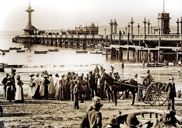 The Pier, Rogge Bay, Cape Town. Sundays were a favoured day for outings on the Pier at the end of Adderley Street. In this photo from the early 1900s, people gather on the beach to watch fishermen bring in their catch while a number of small fishing boats lie at anchor at in the lee of the Pier.| Flickr - Photo Sharing!