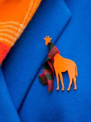 Giraffe Brooch in a Tartan scarf in Orange. http://www.kivimeri.com/brooches/