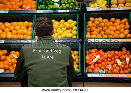 A member of the 'fruit and veg team' working in the Tesco supermarket superstore, Aberystwyth Wales UK (on the opening - Stock Photo