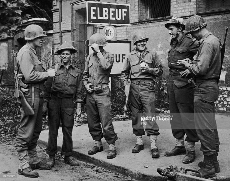US and Canadian soldiers in the liberated town of Elbeuf in France during World War II, circa 1944. They are Private W. R. Burns, Sergeant K. C. Lingetn, Corporal J. E. Juras, Captain A. A. Smith, Lieutenant Clair Jones and Sergeant L. R. Huntingdon.