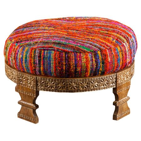 Featuring an oval silhouette and variegated upholstery, this charming ottoman adds a pop of color to your living room or home library.