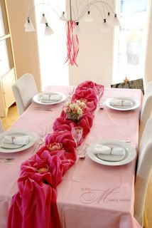 A Light Pink Shiny Fabric Covers A White Table Cloth And The Hot Pink Fabric  Is