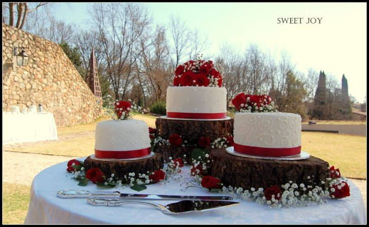 Red wedding cake with piping detail on tree stump cake stands