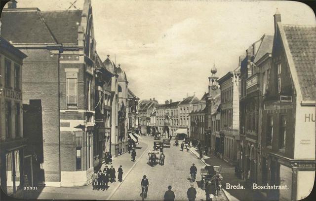 Breda. Boschstraat uit de jaren 20. Op de foto zien we veel mannen in pak met hoed, Hotel De Kroon, oude auto's en handkarren.