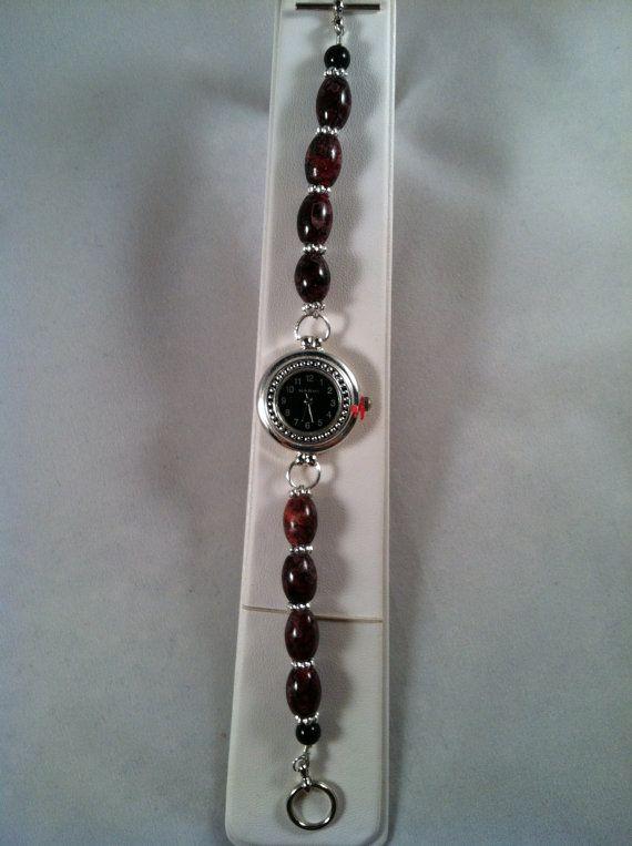 Diese Uhr sieht gut mit schwarz, braun, grau oder rot. Das schwarze Gesicht ist von einem silbernen Lünette umgeben. Die hübschen roten Jaspis Accemt Perlen werden durch Silber Spacer Perlen und ein antikisiert Silber Toggle hervorgehoben. 7.5 lange.  In unseren Schmuck verwenden wir sehr starken und haltbar biegsamen Draht. Wir arbeiten in erster Linie mit nur Glas, Schale und Stein und Swarovski-Kristall-Perlen. Verwendung von Acryl ist sehr begrenzt. Es gibt keine Acryl-Perlen, die auf…