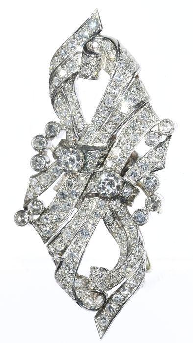 Late Art Deco platinum en diamond dubbele clip broche met een gewicht van de totale diamant 4.80 ct.  Soort juweel: dubbele clip broche. De broche heeft een verwisselbare pinback te scheiden van de clips.Voorwaarde: uitstekendLand van herkomst: NederlandGeïnspireerd door: Art DecoPeriode: ca. 1950Materiaal: platinaDiamanten: 2 briljant geslepen diamanten met een totaal gewicht van ca. 060 ct en 136 enkel geslepen diamanten met een totaal geschatte gewicht van 4.20 ct.Kleur en helderheid: F/G…