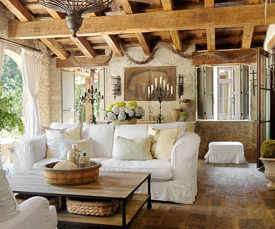 Tuscan Dream - Reclaimed wood ceiling beams, wrought-iron accents, and stone flooring convey old-world style in this sunporch. French doors along one side of the room welcome visitors from the inside. On the opposite wall, heavy curtains can be thrown open to welcome fresh breezes or closed if the space ever feels chilly.