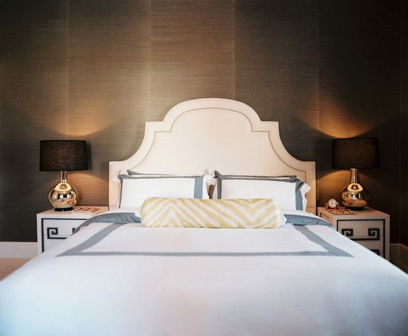 A white upholstered headboard and grass-cloth wallpaper in a bedroom